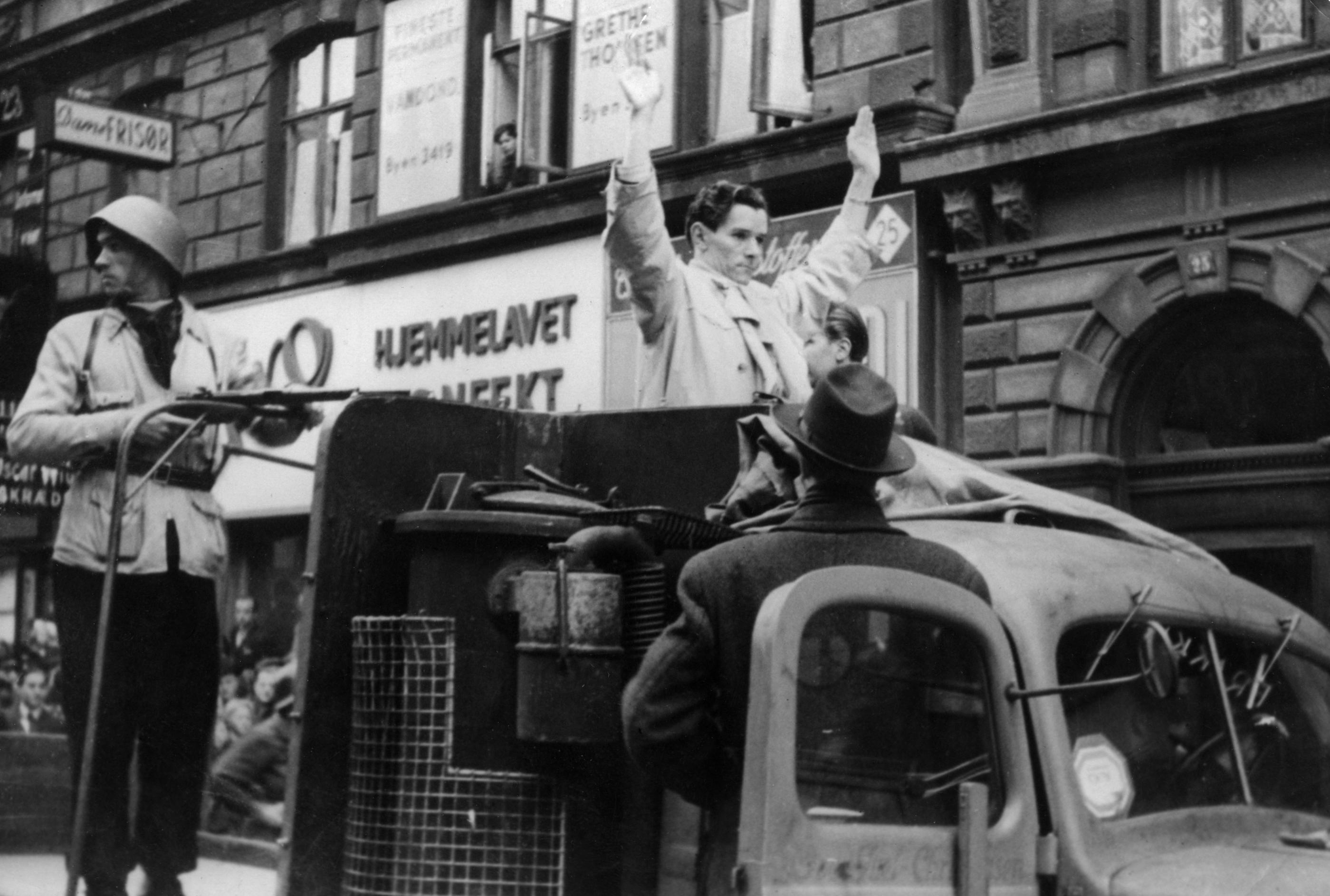 En man i hjälp riktar gevär mot en annan man som håller upp händerna i luften. Foto: SVT Bild.
