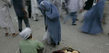 En kvinna i Kabul försöker köpa bröd av en man som sitter vid vägkanten.  Foto: Rafiq Maqbool/Scanpix.