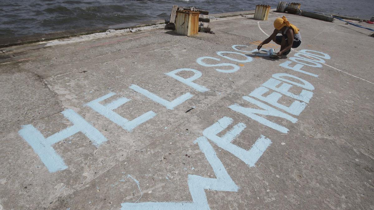 En man skriver ett nödrop om hjälp i hamnen i den totalförstörda staden Tacloban. Foto: Aaron Favila/TT.