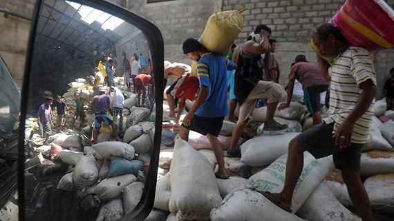 Invånare i staden Tacloban plundrar ett lagerhus och tar med sig säckar med ris. Foto: Noel Celis/TT.