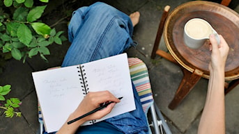 Nainen kirjoittaa ja juo kahvia. Foto:  JESSICA GOW / SCANPIX