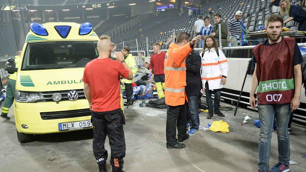 Skadade tas om hand sedan en läktare rasat samman på Djurgårdsklackens sida under matchen mellan AIK och Djurgårdens IF på Friends Arena på onsdagen. Foto: Maja Suslin / TT