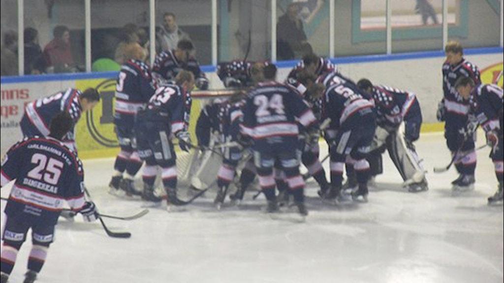 Ishockeyspelare samlade runt målvakten.