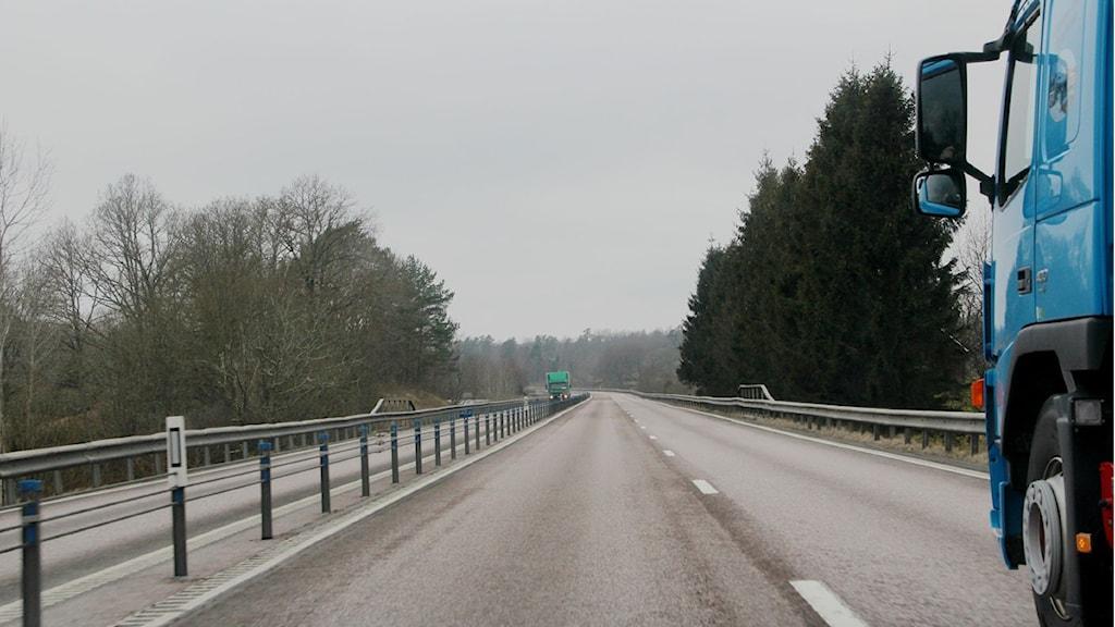 fotografiet taget i en omkörning av en lastbil: lastbilens framdel skymtar till höger i bild, ett vägräcke i mitten och längre fram kommer en mötande lastbil i motsatt riktning