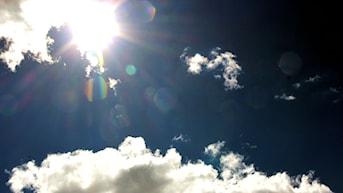 Solen tittar fram bakom ett par fluffiga vita moln. Foto: Stina Linde/Sveriges Radio.