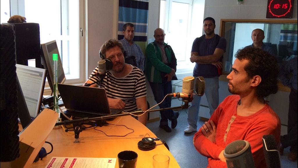 Mattias Nilsson intervjuar Kader Nijim i sändingsstudion. I bakgrunden står andra deltagare i projektet. Foto: Jennie Konrad / Sveriges Radio