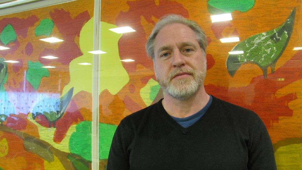 Ulf Guttormsson står mot en multifärgad vägg och ler. Han står i bildens högra fält.
