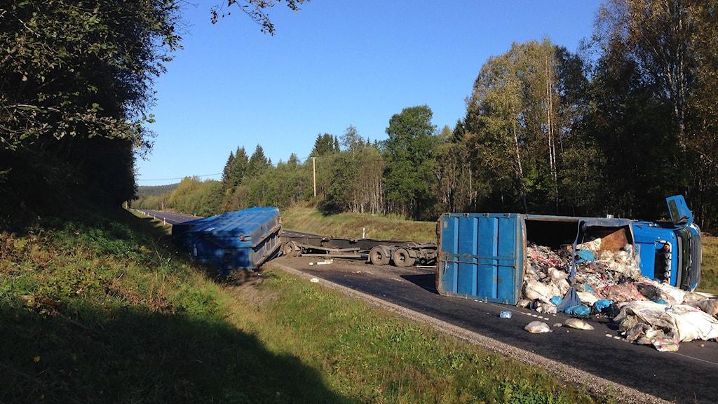 Olycka E14 vid Nedansjö. Containerbil lastad med sopor ligger tvärs över vägen. Foto: Niklas Axelsson/SR