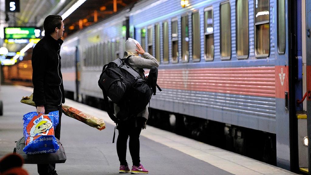 Resenärer med julklappar väntar på tåg från Stockholms Central på fredagskvällen. Foto: Anders Wiklund/Scanpix