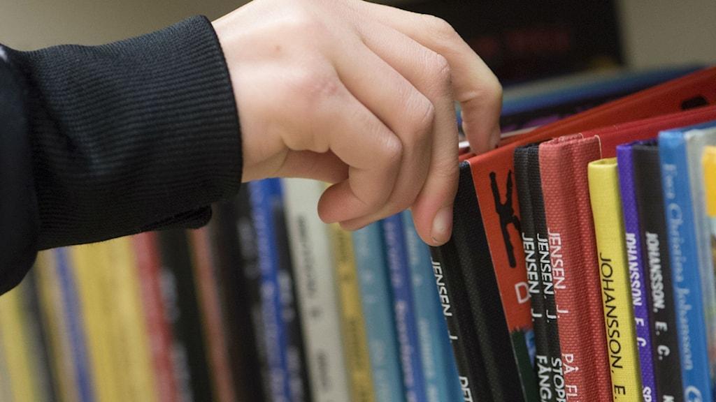 Hand som tar ut en bok från en bokhylla. Foto: Fredrik Sandberg/TT.