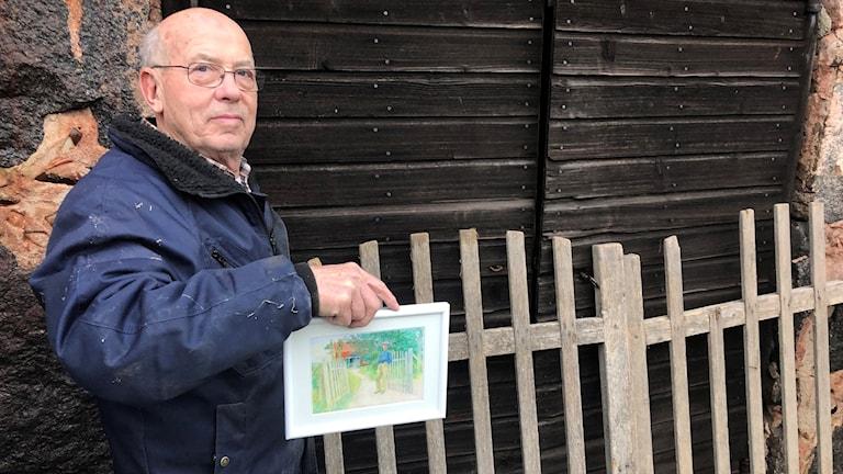 Dag Larsson visar målning av konstnären Carl Larss...
