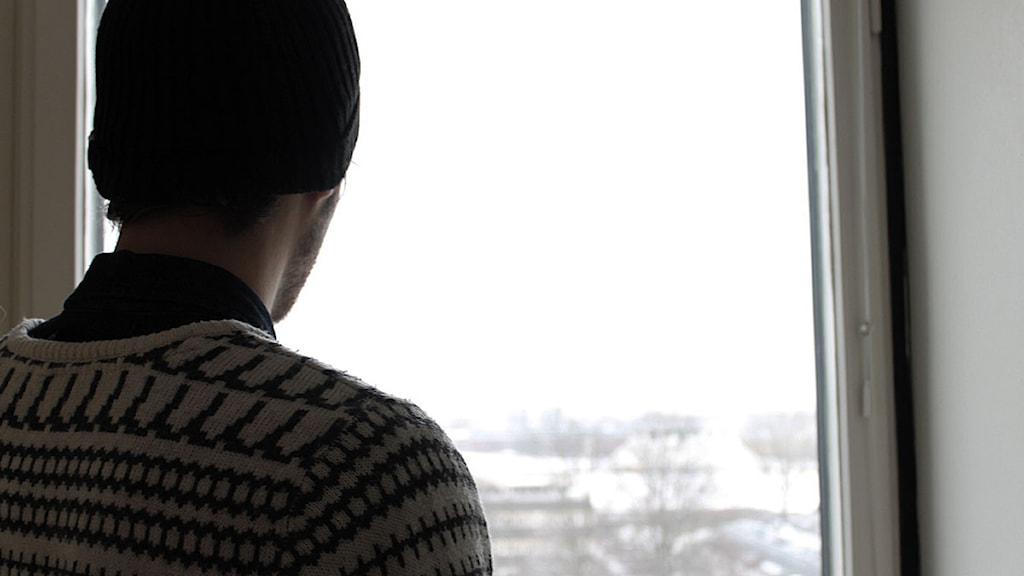 En ensam kille ser ut genom ett fönster