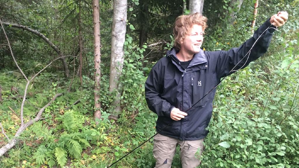 Rolf Nylinder monterar upp ett flugspö i en skog utanför Umeå. Foto: David Carr/Sveriges Radio