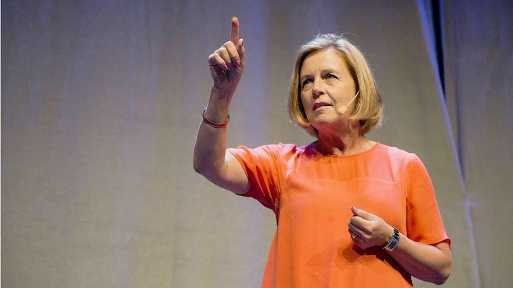 Kansanpuolueen puoluesihteeri Maria Arnholm osoittaa sormella ylöspäin oranssissa paidassaan.