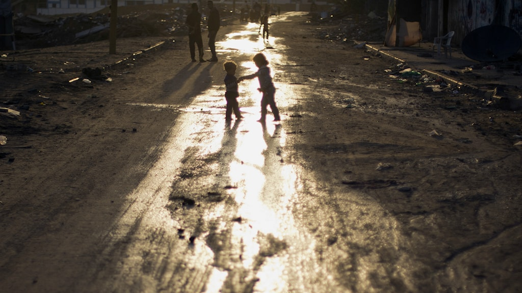 Palestinian children play on the street as the sun sets over the town of Beit Hanoun, the northern Gaza Strip, Sunday, Oct. 19, 2014.