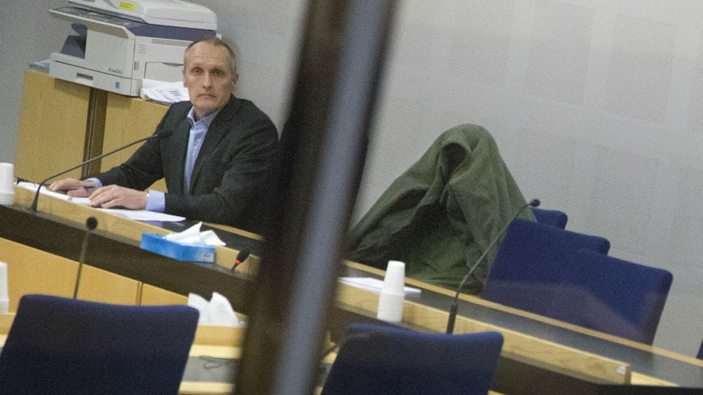 The 27-year-old at the remand hearing, covered by a green coat. The hearing then continued behind closed doors. Photo: Björn Larssson Rosvall/TT