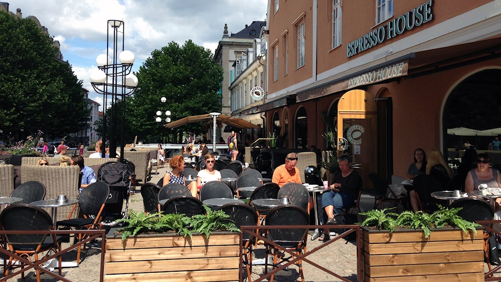 Många människor sitter ute på uteserverinagrna och fikar i solskenet. Foto: Anna Börje