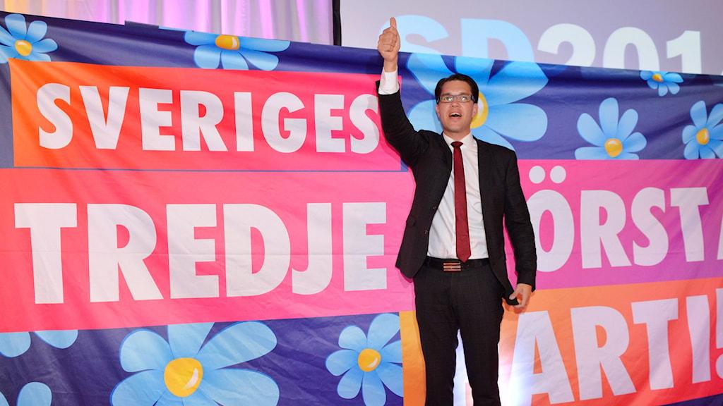 Jimmie Åkesson framför en banderoll med texten 'Sveriges tredje största parti' på Sverigedemokraternas valvaka på Vasavarvet i Stockholm på söndagskvällen. Foto: Anders Wiklund / TT