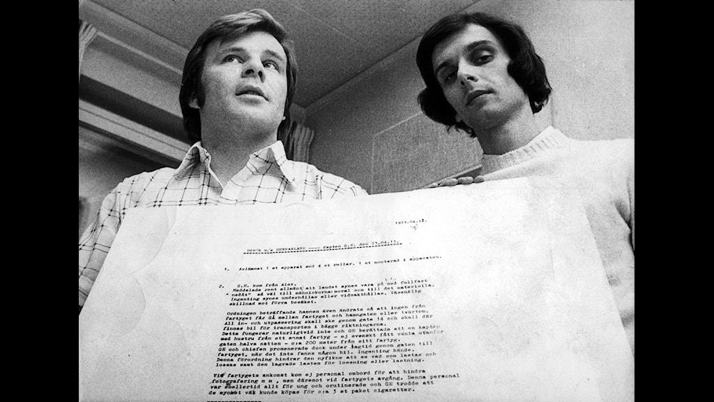 1973-05-15. Jan Guillou och journalistkollegan Peter Bratt. Guillou (t.v.) och Bratt, journalister på tidningen Folket i Bild/Kulturfront, ses här med ett uppförstorat dokument som visar hemliga underättelserapporter i samband med IB-afffären. Foto: SCANPIX