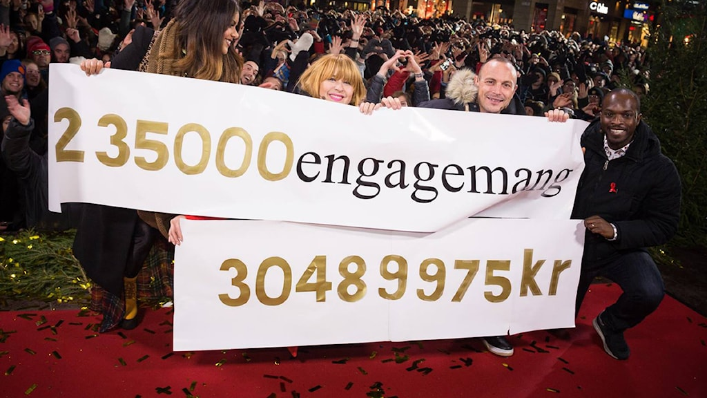 Arantxa, Linnea, Petter och Kodjo. Med banderoll där det står 235 000 engagemang och 30 489 975 kronor. Foto: Sveriges Radio.