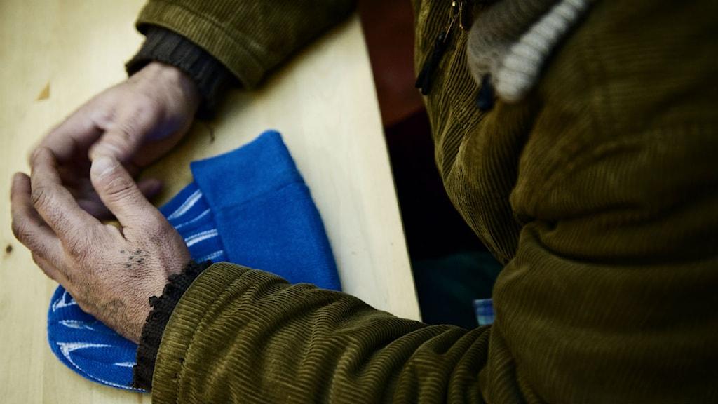 En ensam mans händer vilar på en mössa. Foto: Jens L´Estrade/SCANPIX