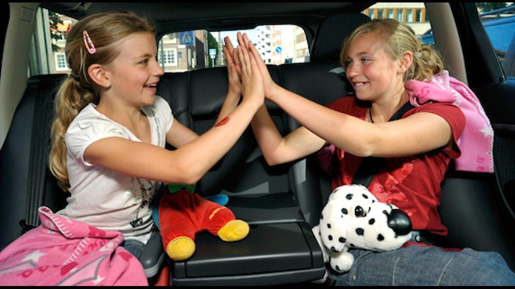 Två flickor leker lekar i baksätet på en bil Foto: Janerik Henriksson / SCANPIX