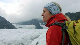 Forskaren Gunhild Rosqvist blickar ut över Storglaciären i Tarfala. Mörkt berg sticker ut genom den vita glaciären och himlen är molnig.