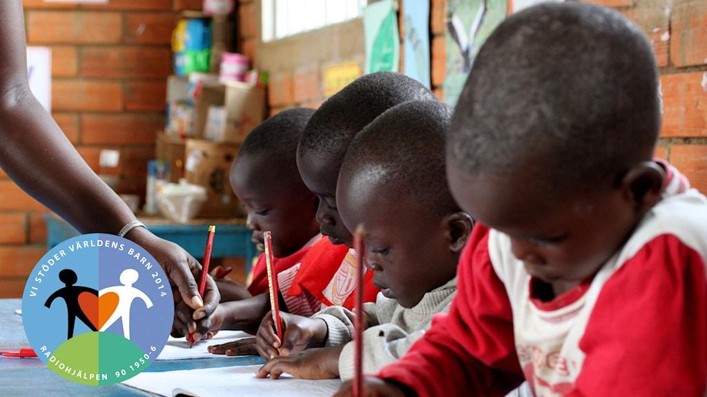 Barn som sitter och skriver i ett klassrum i Uganda. Foto: Erikshjälpen.