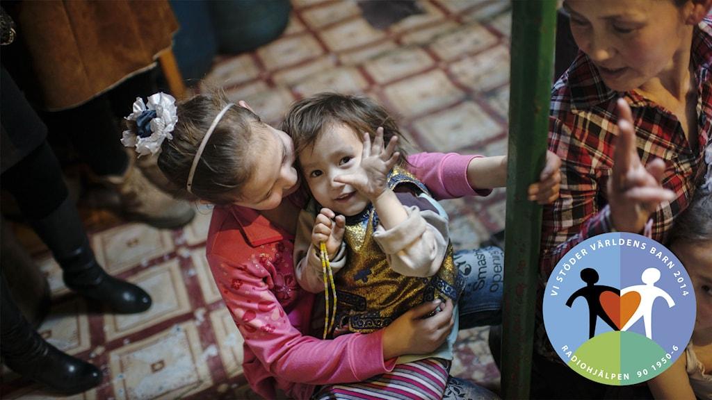Ett litet barn sitter i knät på ett större barn i SOS barnbyar i Mongoliet. Foto: Maja Brand.