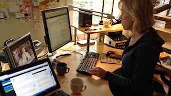 Ginna Lindberg framför datorn. Foto: Nils Lindström/Sveriges Radio.