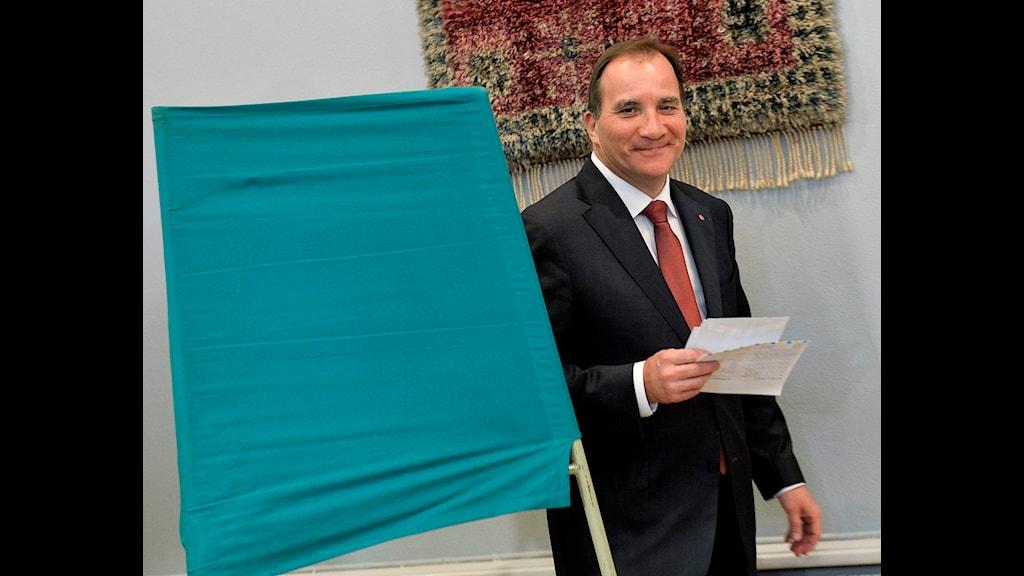 Stefan Löfven står vid en grön skärm. Han har några papper i handen.