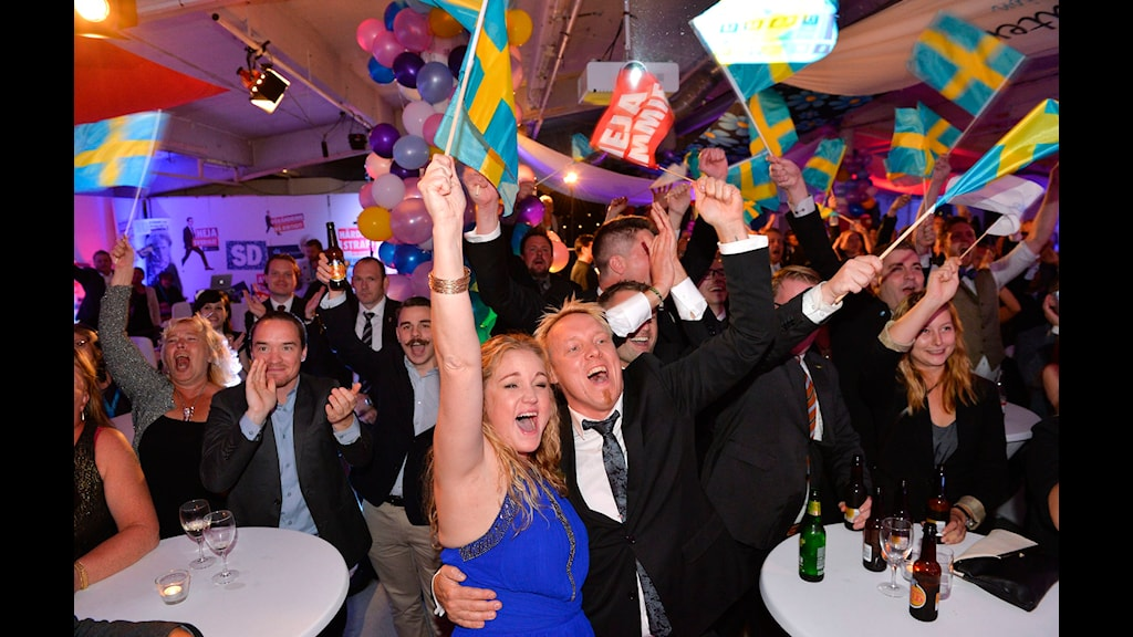 De jublar och viftar med svenska flaggor.