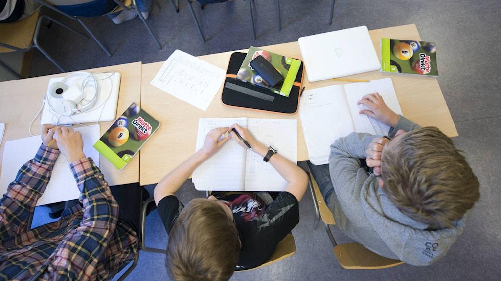 Tre elever sitter vid skolbänken med sina matteböcker