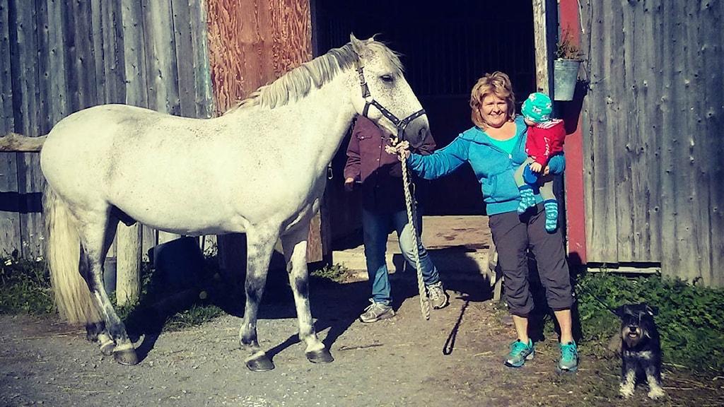 Karin Hemmingsson med ett barn i famnen och håller i en häst.