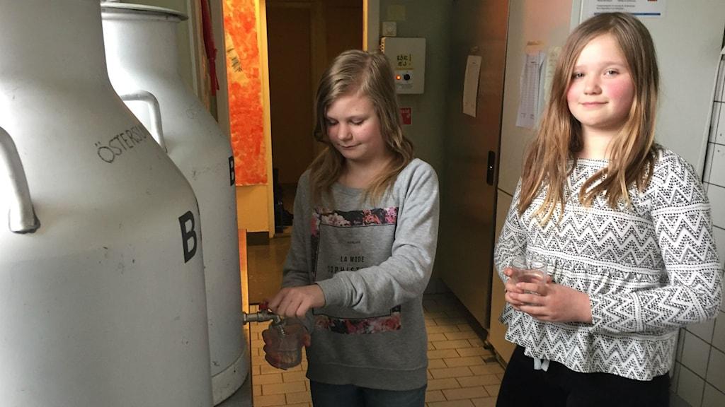 Två elever som tappar upp vatten
