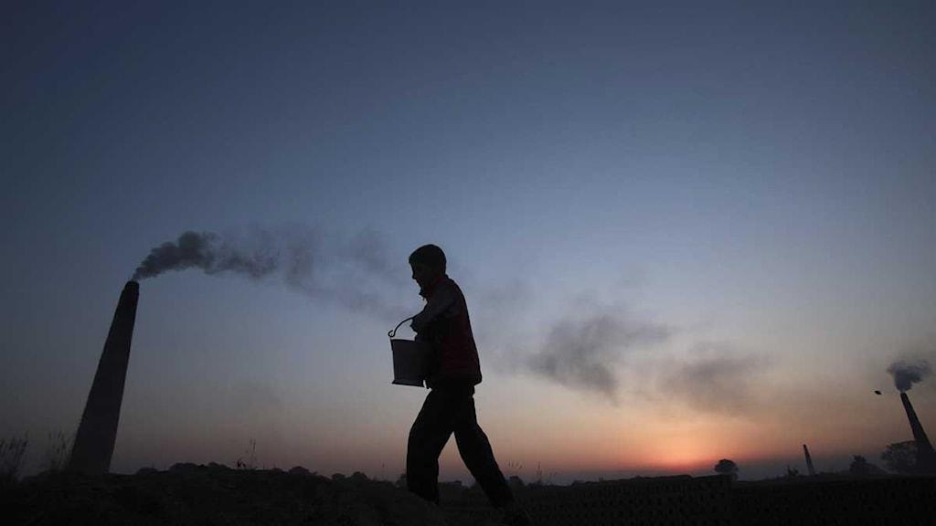 En pojke går förbi en indisk tegelfabrik. Foto: Channi Anand/Scanpix.