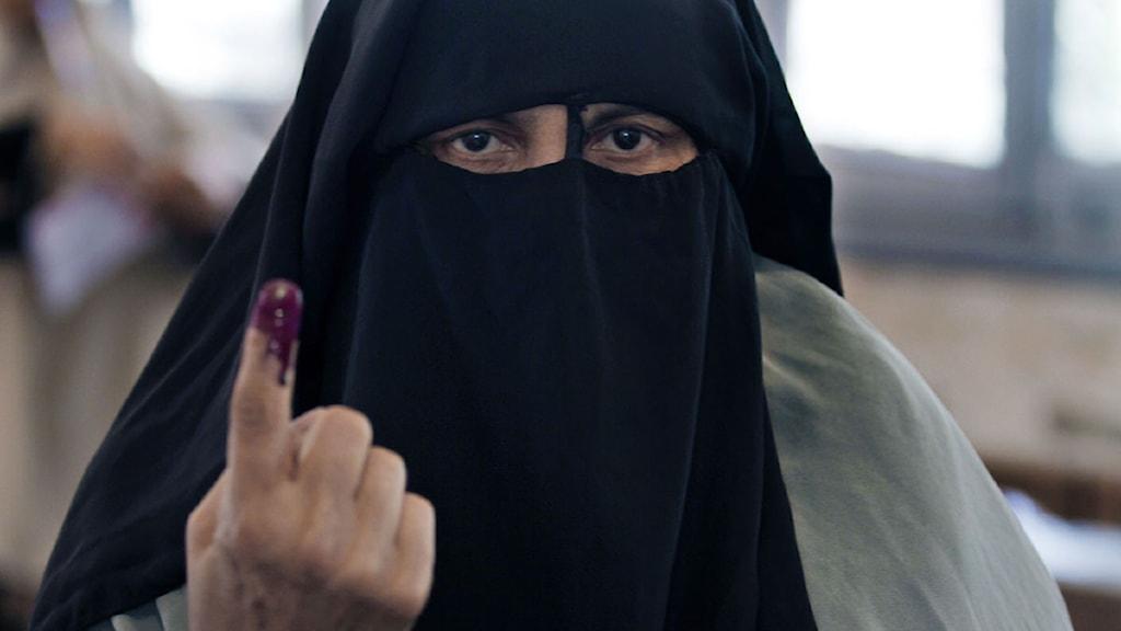 En egyptisk kvinna visar sitt finger med bläck på efter att ha röstat i presidentvalet. Foto: Khalil Hamra/Scanpix.