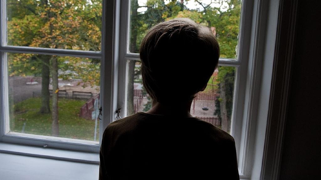 En pojke står och tittar ut genom ett fönster. Foto: Jonas Ekströmer/Scanpix
