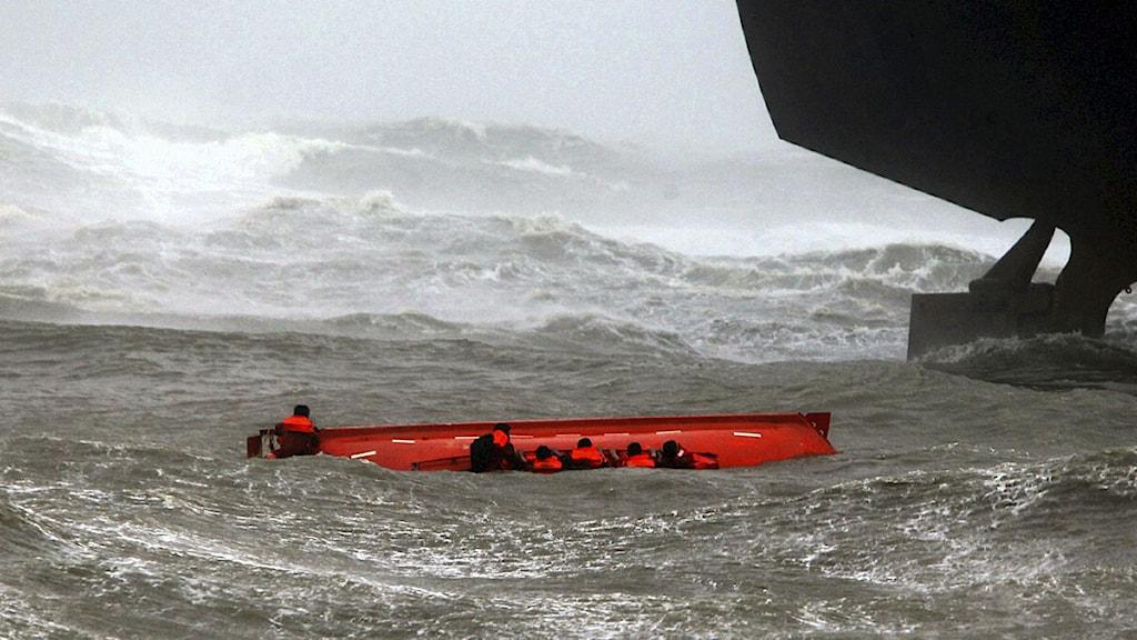Besättningsmän från oljetankern Pratibha Cauvery klamrar sig fast vid en livbåt efter en grundstötning utanför stadens Chennais kust.
