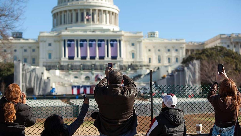 Besökare står utanför Vita huset, där man förbereder inför att Barack Obama ska svära presidenteden för andra gången. Allison Shelley/Scanpix.