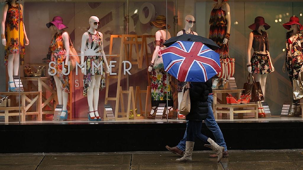 Ett par går förbi en klädbutik i London. Foto: Matt Dunham/Scanpix.