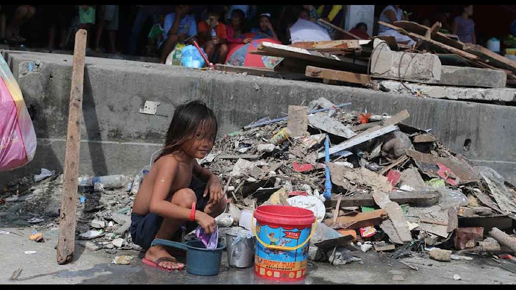 Liten flicka tvättar kläder framför Astrodome-stadion i Tacloban.