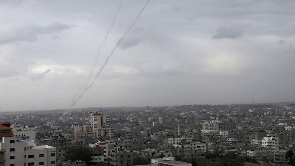 Rök från raketer som skjutits upp av militanta palestinier mot Israel syns ovanför Gaza City. Foto: Adel Hana/AP/TT.