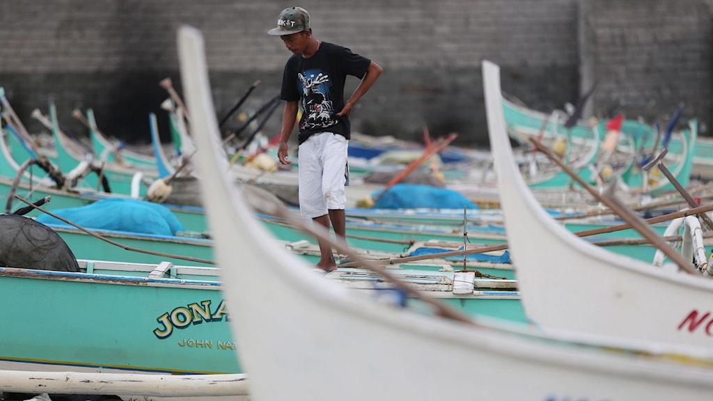 Man går vid båtar i Filippinerna
