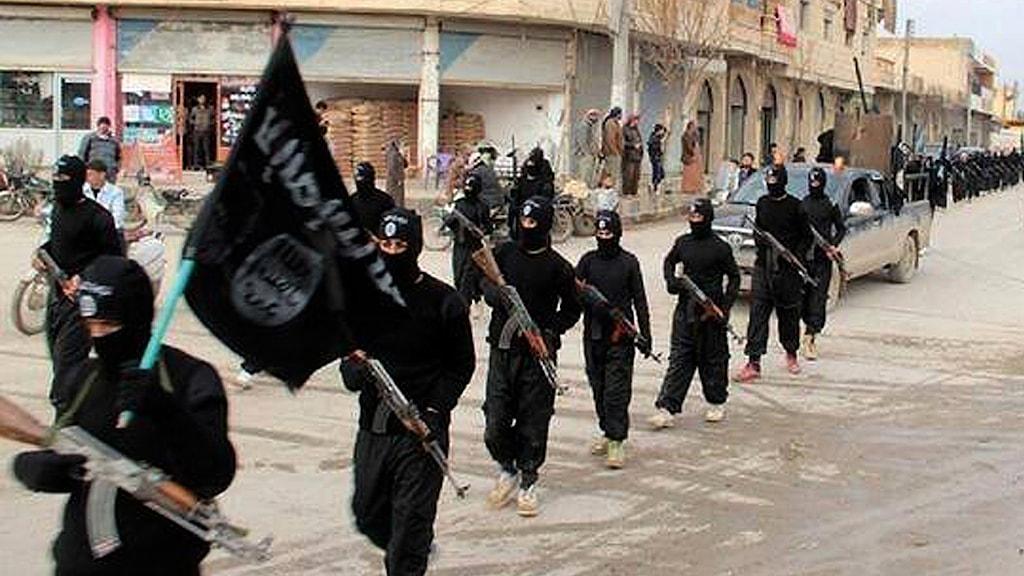 En grupp Isis-soldater marscherar genom ett samhälle. Foto: TT