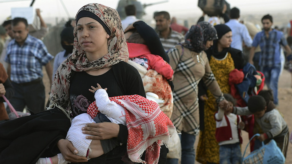 Syriska flyktingar samlas vid gränsen mot Turkiet, lördagen 20 september 2014. Foto: AP/TT.