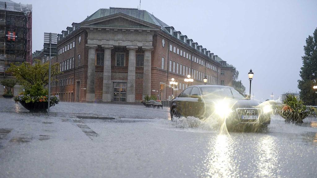 En bil plöjer fram genom vattnet i centrala Stockholm. Foto: Jessica Gow/TT.