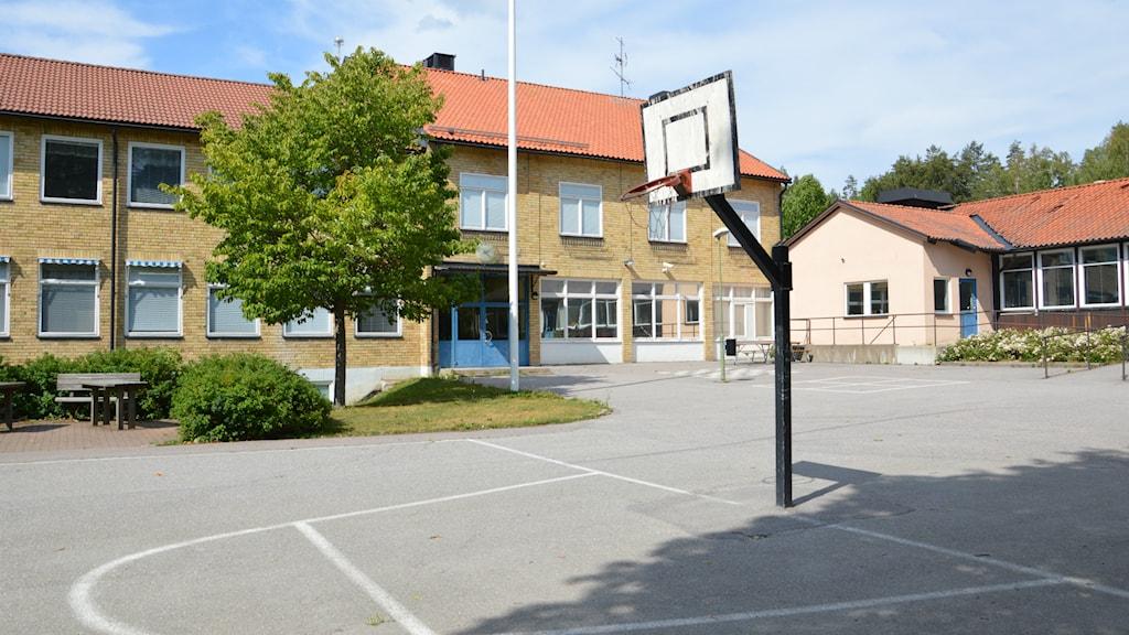 Skolgård med basketkorg, i bakgrunden gula tegelbyggnader. Foto: Petra Levinson/Sveriges Radio.
