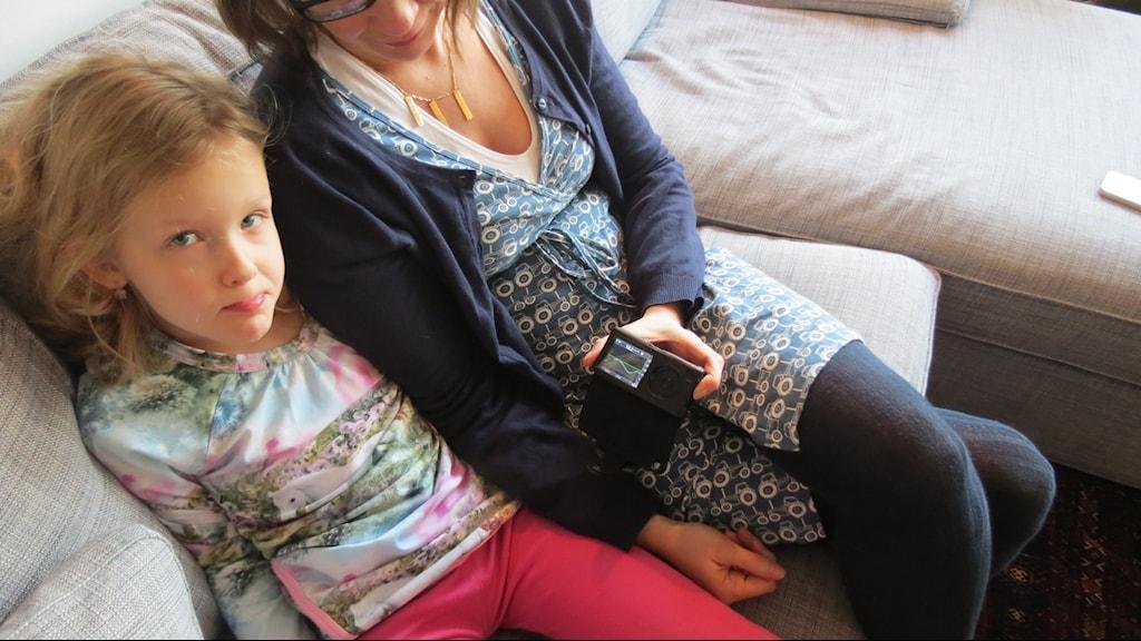 Billedet viser Klara Bolinder, syv år, i Hjärup. Hun har type 1-diabetes. Ved siden af sidder mor Gundela Bolinder med glukosemåleren Dexcom i hånden. Måleren holder styr på Klaras blodsukkerværdier. Foto: Petra Haupt/Sveriges Radio.