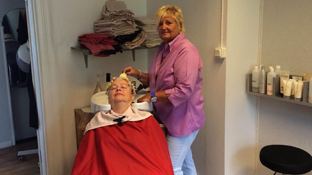Frisören Gunilla och kunden Lena pratar politik samtidigt som Lena får sitt hår permanentat. Foto: Alexander Zeilon Lund/SR